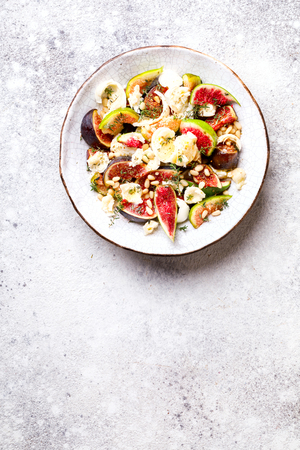 Salad with figs Mozzarella Thymean, Cedar Nut and honey.Healthy Food on the Stone Background. Nutrition Concept.Top View.Copy space for Text.