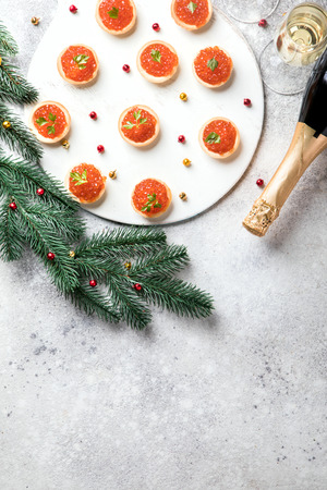 Christmas and New Year holidays composition. Red Salmon Caviar in Tartlets. Festive Appetizer and champagne on  gray background.Copy space for Text.
