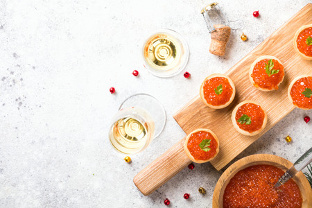 Christmas and New Year holidays composition. Red Salmon Caviar in wooden bowl, Tartlets Festive Appetizer and champagne on  gray background.Copy space for Text. Stock Photo
