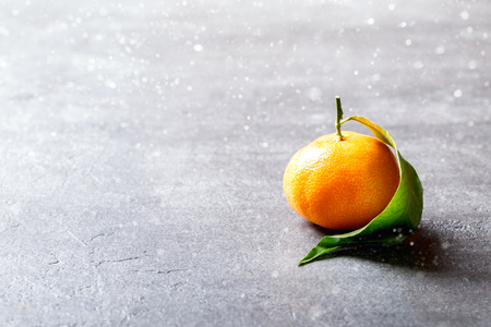 Fresh delicious mandarin, tangerine, clementine with green leaf on gray background. Ripe citrus fruits.Creative minimalistic food concept.Drawn Snowfall. Copy space for Text. Zdjęcie Seryjne - 112891178