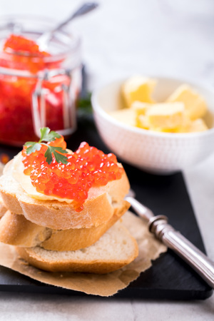 Salmon red caviar in a glass jar and Sandwiches with butter and parsley on slate cutting board on a light marble background. Seafood. Healthy Food Concept. Snack. Imagens