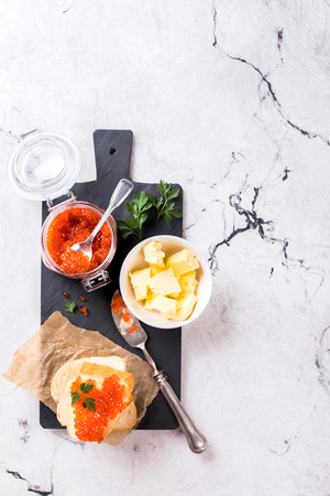 Salmon red caviar in a glass jar and Sandwiches with butter and parsley on slate cutting board on a light marble background. Seafood. Healthy Food Concept. Snack.Copy space for Text.
