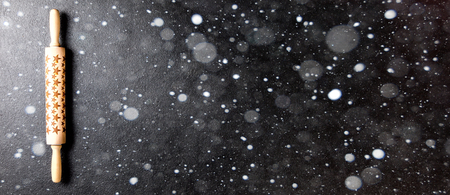 Rolling pin with a pattern in the form of stars on a black board. Baking Background Christmas holidays composition.Concept for Menu, Recipe, Ingredient. Copy space for Text.Drawn Snowfall.Banner