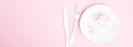 Festive table setting for Valentine's Day with fork, knife and hearts  on pink pastel background.Romantic dinner. Space for text. Top view.Banner. Banco de Imagens