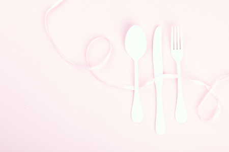 Festive table setting with fork, knife and hearts  on pink pastel background.Romantic dinner. Space for text. Top view. Stock Photo