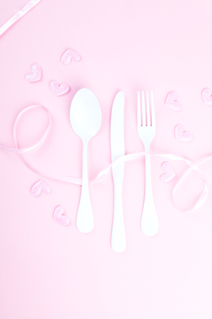 Festive table setting for Valentines Day with fork, knife and hearts  on pink pastel background.Set of silverware .Romantic dinner. Space for text. Top view
