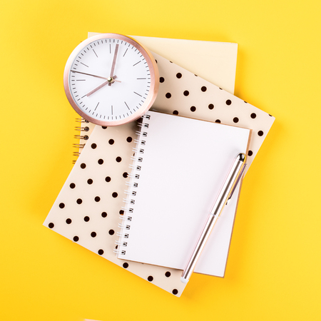 Ð¡lipboard,Notebook ,pen and alarm clock on a bright yellow background.Accessories office concept.Business Idea. Time to school.Top View.Flat Lay. Copy space for Text.