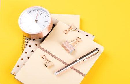 Notebook, pen and alarm clock on yellow