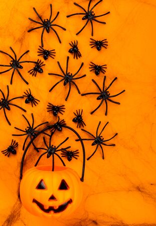 Halloween postcard. Тraditional festival of autumn. Decoration and party concept. Orange pumpkin on a background with a black web and spiders. Flat lay, top view, copy space