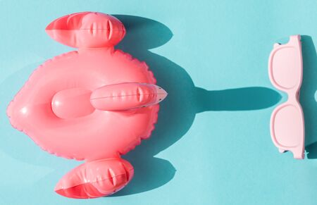 Beach accessories on blue background. Pink inflatable flamingo and white glasses.Summer vacation. Creative concept.Travel mood to the sea.Harsh sunlight shadow.Flat lay.