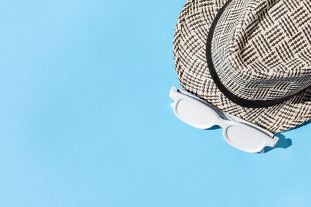 Beach accessories on blue background. Hat and sunglasses.Summer vacation. Creative concept.Travel mood to the sea.Flat lay.