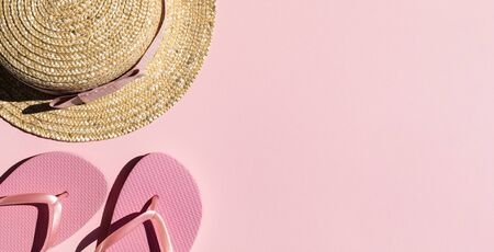 Beach accessories on pink background. Flip flops, hat.Summer vacation. Creative concept.Travel mood to the sea.Flat lay.Banner