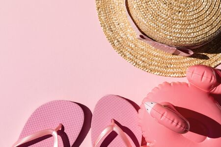 Beach accessories on pink background. Flip flops, hat and sunglasses.Summer vacation. Creative concept.Travel mood to the sea.Flat lay 写真素材