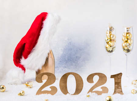 New Year's festive card with numbers 2021. Composition Champagne bottle in Santa Claus hat with glasses and traditional decorations.Light winter background.