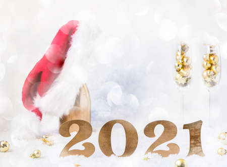 New Year's festive card with numbers 2021. Composition Champagne bottle in Santa Claus hat with glasses and traditional decorations.Light winter background.Light Effect Boke