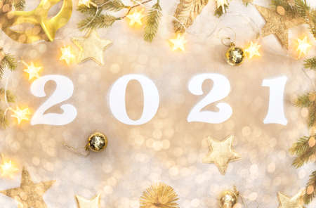New Year Flat Lay composition Shining Holiday card with Holiday card with numbers 2021 Celebration on a gold background. Holiday party decoration.Flat lay, top view, copy space.