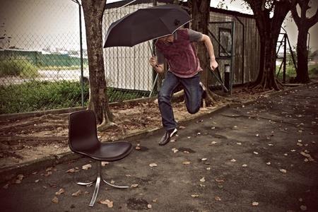 man: Man holding umbrella jumping Stock Photo