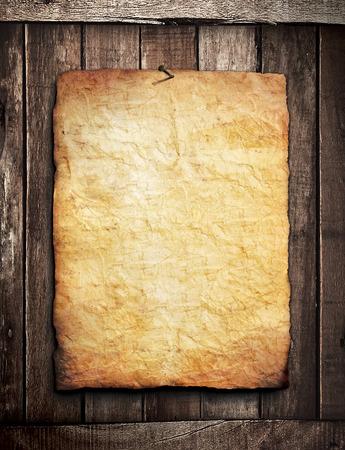 Old grunge paper on wooden wall Standard-Bild