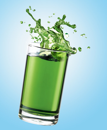 jugo verde: Green juice splashing from glass
