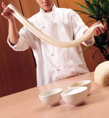 chinese noodles: Chinese chef making fresh noodles Stock Photo