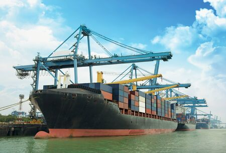 Cargo ship and container box over shipping dock Imagens