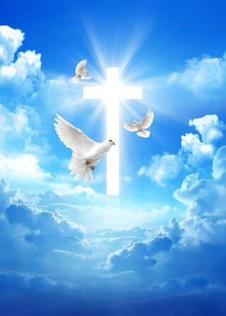 Taube über einem Kreuz im Hintergrund des bewölkten Himmels mit Lichtstrahlen Standard-Bild
