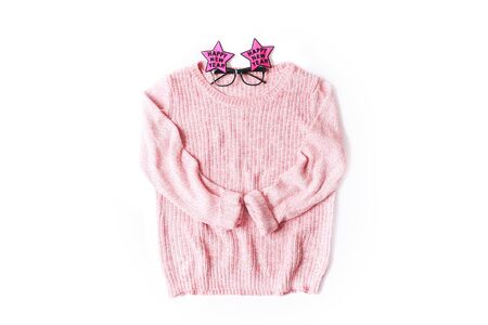 Pink knitted sweater with festive New Year glasses isolated on white
