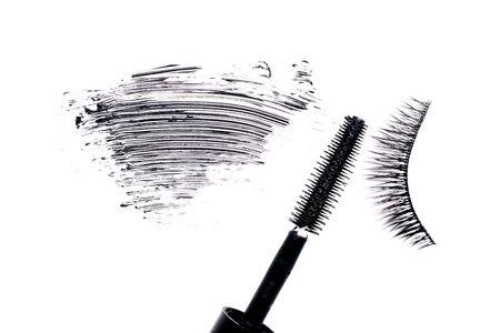 Mascara brush with mascara stroke and fake false eyelash on white background