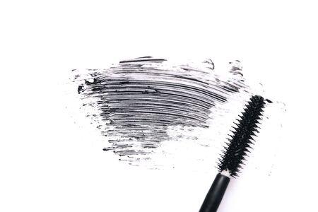 Mascara brush with mascara stroke on white background