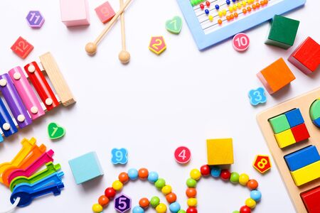 Frame of colorful kids toys on white background. Top view, flat lay. 免版税图像