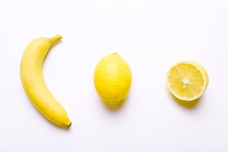 Banana and lemons in row on white background Stock Photo