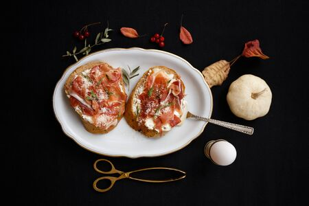 Bruschettas with prosciutto, smoked meat over a black backdrop. Top view Banque d'images