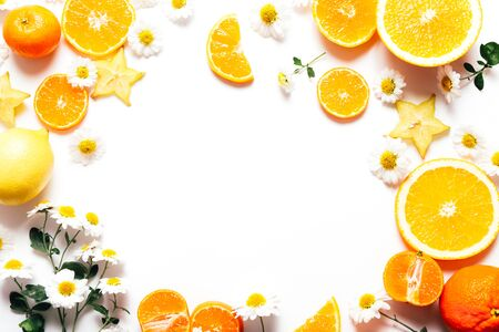 Frame of sliced oranges and tangerines with flowers on white background, copy space Foto de archivo