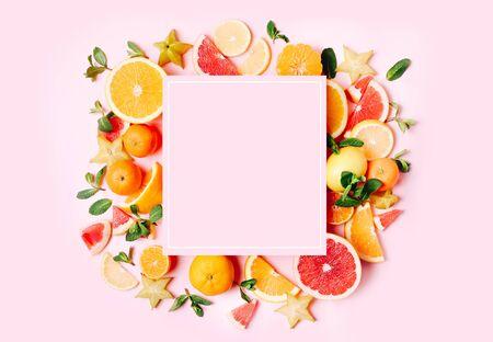 Fresh citrus fruits formed frame on pink background. Copy space. Mock up