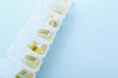 Open daily pill box on blue background.