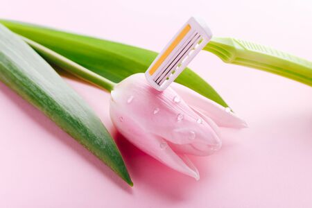 Green razor with beautiful pink tulip on a pink background. Hair removal concept.