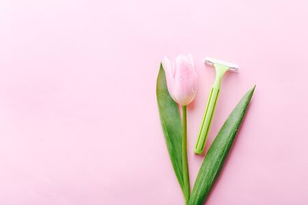 Green razor with beautiful pink tulip on a pink background. Hair removal concept. Standard-Bild