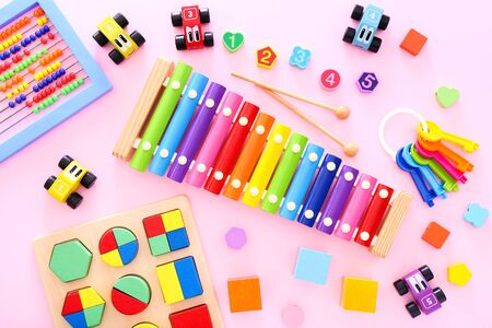 Colorful kids toys on pink background. Top view