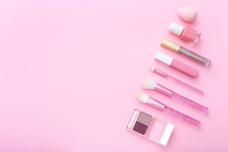 Makeup products on pink background.