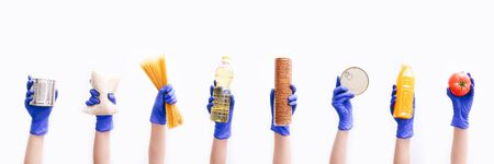 Hands in blue rubber gloves hold different food on white background. Donation concet. Food supplies for the period of quarantine on white background. Food delivery concept.