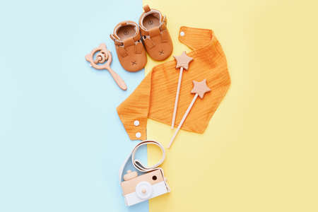 Set of baby stuff and accessories on light blue and yellow background. Baby shower concept. Fashion newborn. Flat lay, top view