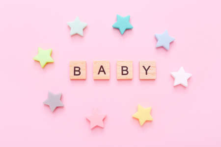 Wooden blocks with word Baby and little colorful stars around it on pink background. Top view Stockfoto