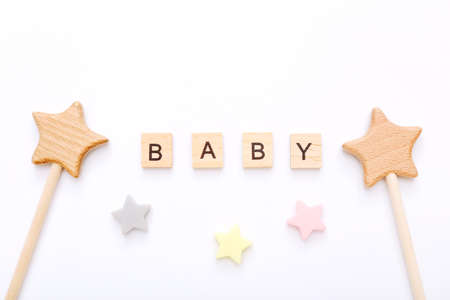 Wooden blocks with word Baby and little stars near it on white background. Top view