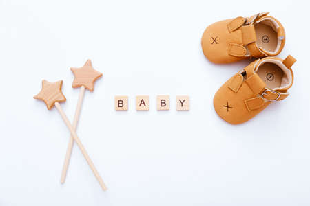Wooden blocks with word Baby, booties and wooden stars near it on white background. Top view Stockfoto