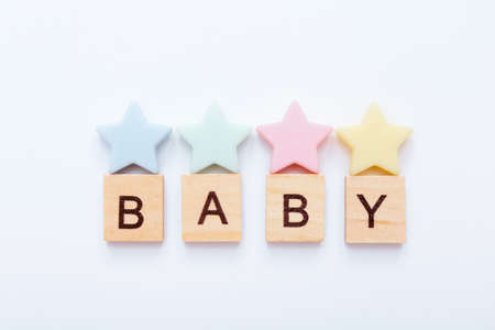 Wooden blocks with word Baby and little colorful stars under it on white background. Top view
