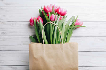 Shopping craft bag with pink tulips on white wooden background. Zero waste concept