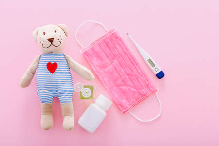 Protective medical mask with a bear toy, thermometer, and hand sanitizer on a pink background. Concept of quarantine of schools, home education