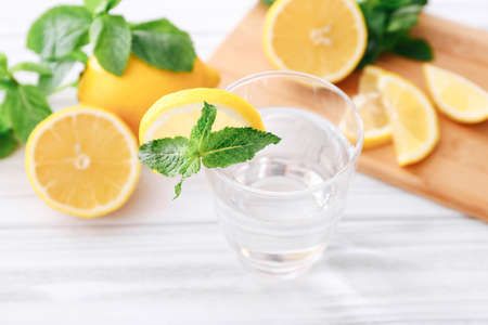 Full glass of fresh cool transparent water with lemon and mint leaves