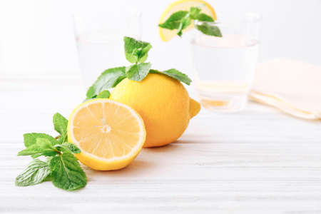 Lemon and mint leaves on wooden table and glasses of water