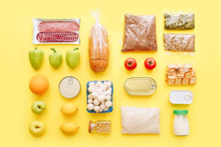 Set of grocery items from canned food, vegetables, cereal on yellow background. Food delivery concept. Donation concept. Top view.